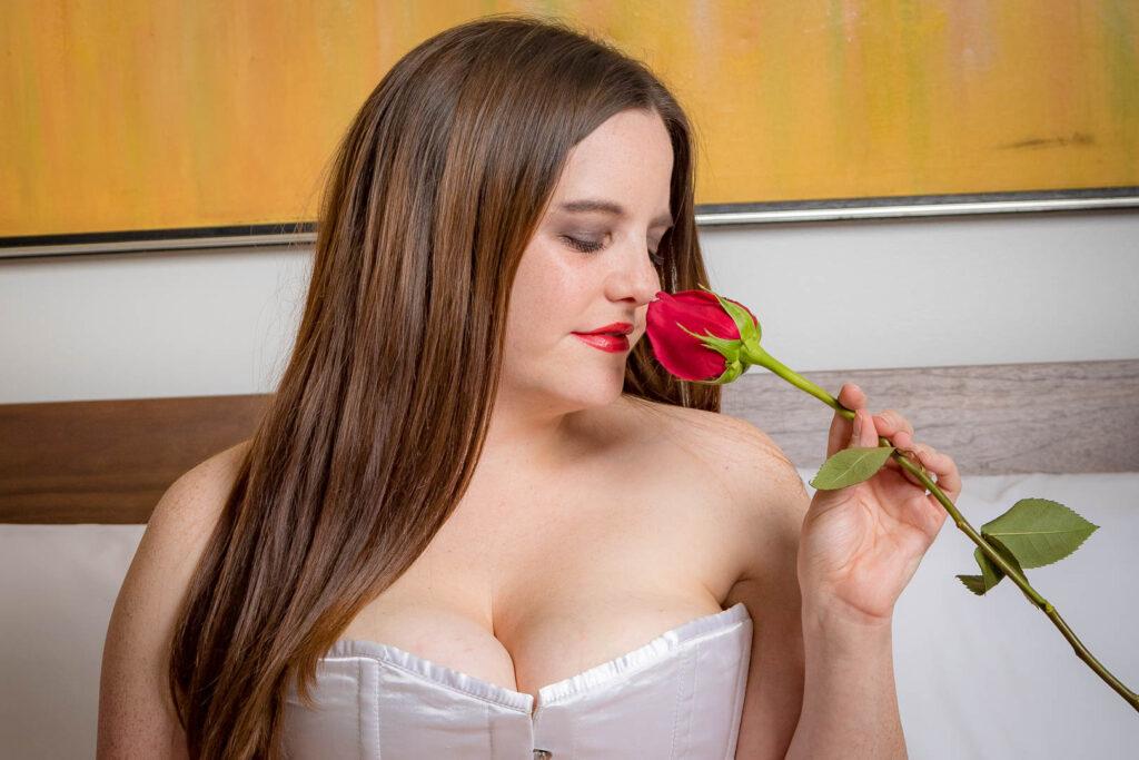 Boudoir - Woman smelling rose wearing a corset